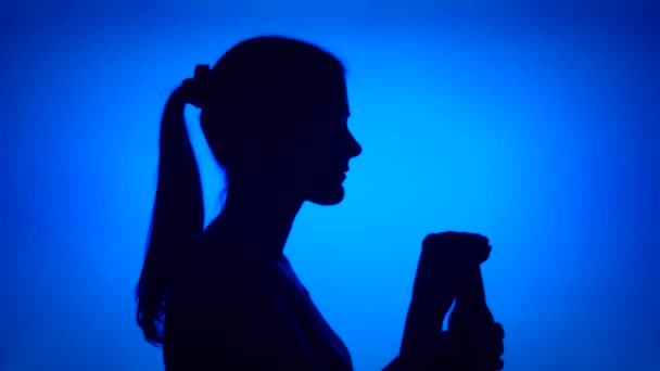 Silhouette of young woman opening beer bottle on blue background. Females face in profile drinking