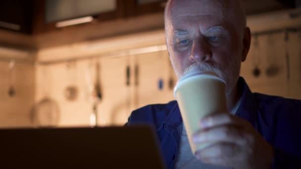 Müde, schläfrig senior Geschäftsmann benutze Laptop im Home-Office. Müde Menschen trinken Kaffee aus Pappbecher