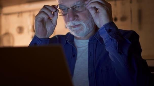 Ältere Mann mit Brille arbeiten am Laptop von Home-Office in der Nacht. Geschäftsmann, die Brille aufsetzen