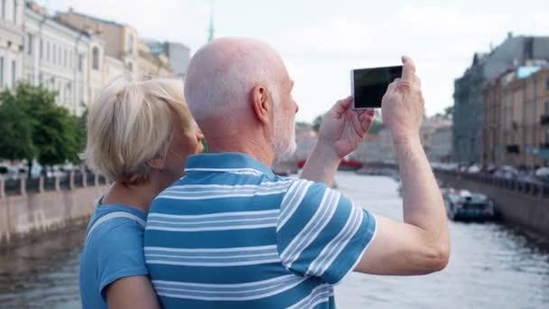 Älteres Paar stehen am Ufer des Kanals nehmen Sie Bilder auf dem Handy in Sankt Petersburg, Russland