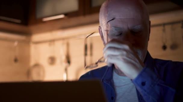 Senior woman arbeiten am Laptop vom home-Office in der Nacht. Geschäftsmann Brille abnehmen und seine Augen reiben
