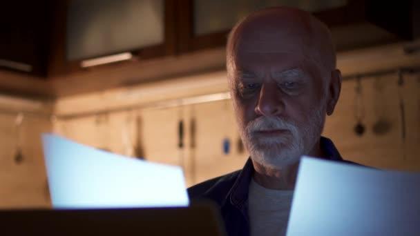 Starší muž na volné noze pomocí přenosného počítače v noci z domácí kanceláře. Přepracovaný podnikatel tvrdě pracuje
