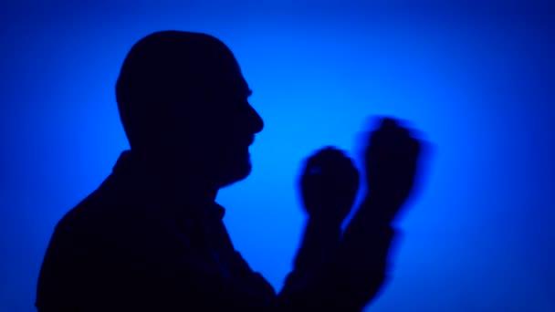 Silhouette eines glücklichen älteren Mannes, der albern auf blauem Hintergrund tanzt. Männer Gesicht im Profil Spaß haben