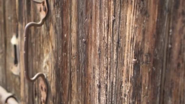 POV člověk pohybovat v zpomalený pohled na pevný hrubý povrch starých dřevěných dveří na slunečný letní den