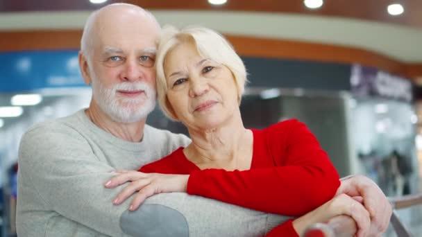 Starší pár stojí v obchoďáku pohledem kamery. Milující, objímání důchodců v obchodní centrum úsměv