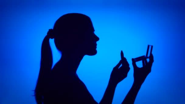 Silueta mladé ženy používat rtěnku. Tvář ženy v profilu se zrcadlem na modrém pozadí