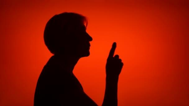 Silueta starší žena dělat mlčení gesto na červeném pozadí. Pojetí záhady a tajemství