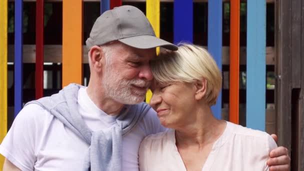 Usměvavá starší pár stojí proti barevné zdi pozadí. Bezstarostné turistické rodiny prožití dovolené