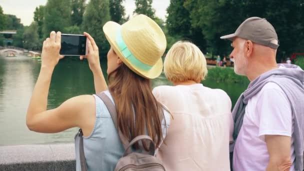 Starší pár a dcera stojí u jezera v parku pořizování fotografií na mobilním telefonu. Rodina si dovolenou