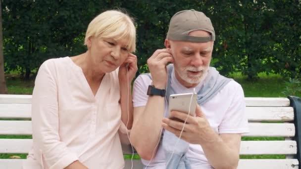 Starší pár mají skvěle sedí na lavičce v parku poslouchat hudbu na smartphonu přes sluchátka