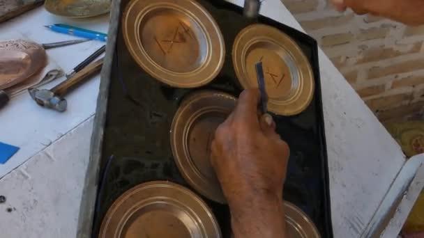 řemeslník gravírování vzory na hlavním panelu. Velitelé střední Asie a v Uzbekistánu. Ruční měděné ražby. staré umění leptání na nádobí