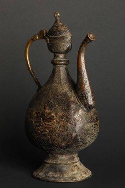 ancient oriental metal teapot on dark background. antique bronze tableware