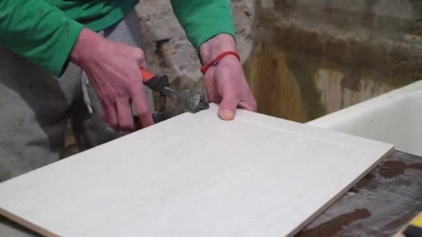Worker with a hand cutter cuts tile. Finishing works, focus on hands. The technology of laying tile.