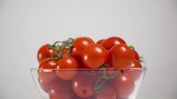 Tomaten mit Stielen in einem Glas auf weißem Hintergrund, kreisförmige Rotation. Nahaufnahme. horizontale Ebene