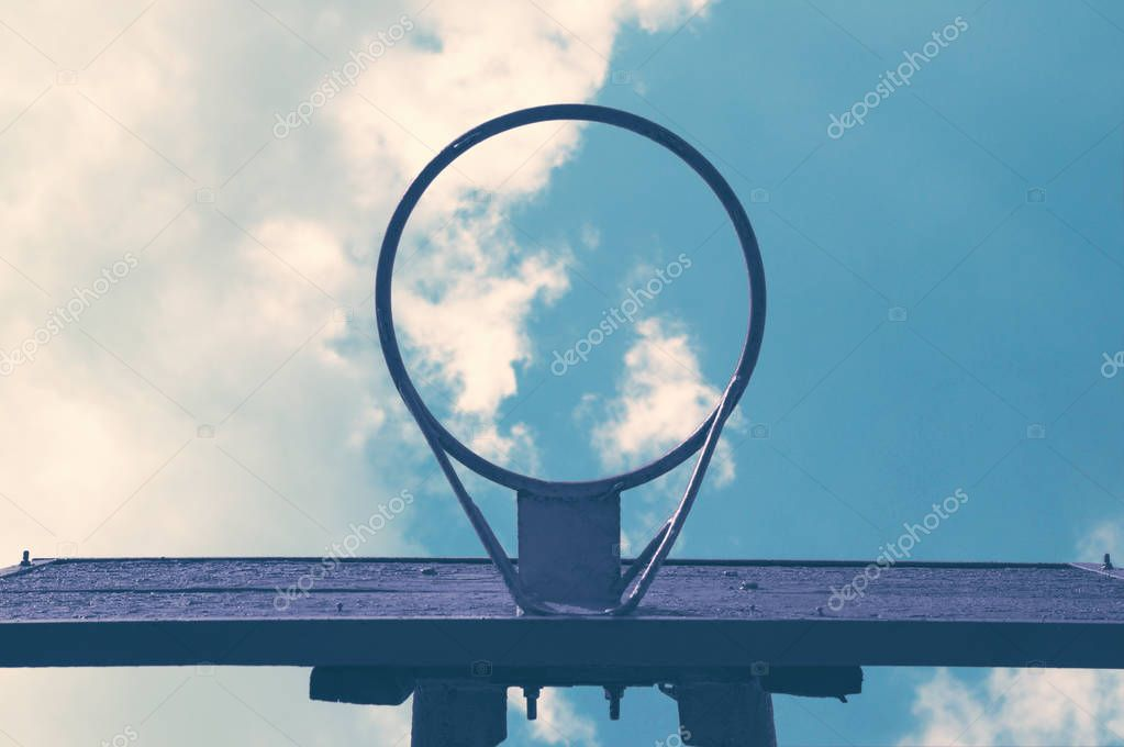 An old basket to play basketball on the background of a daytime bright cloudy sky bottom view
