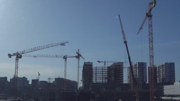 Několik stavebních jeřábů na pozadí jasně modrá obloha