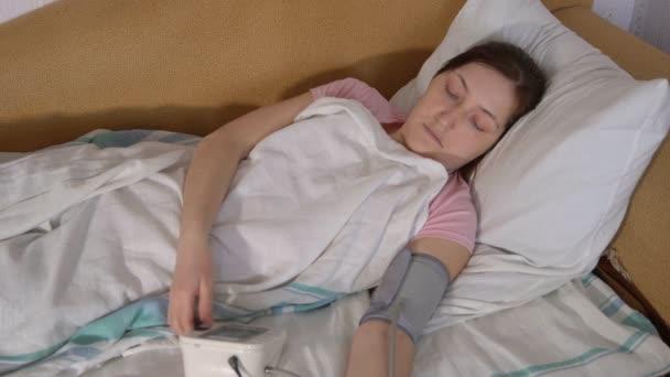 Mladá žena v posteli měří tlak s elektronický tonometr