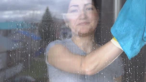 Gyönyörű nő mosás ablak-val egy kék rag és tisztító