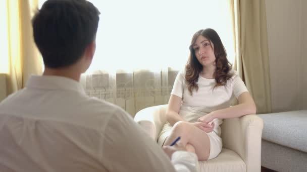 Mladá brunetka žena v recepci s psychologem
