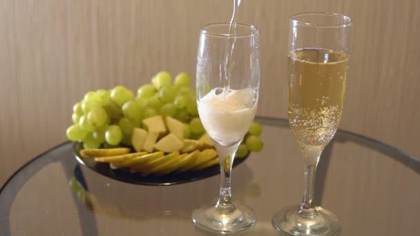 Champagner in Gläsern und ein Teller mit Obst auf dem Tisch