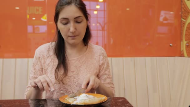 Hezká dívka jí palačinku se zmrzlinou v kavárně, zblízka