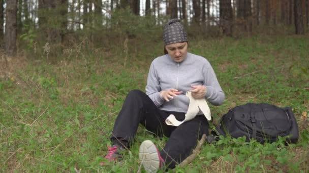 Poranění v přírodě. Mladá žena sama dává první pomoci