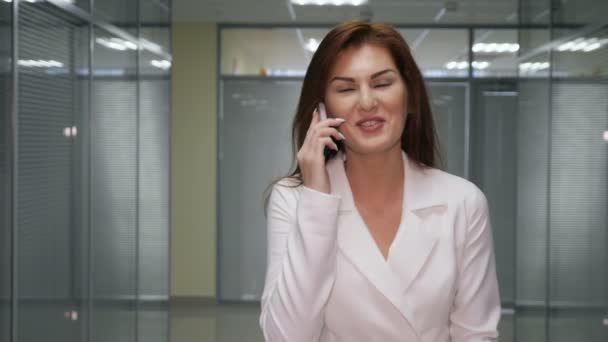 ginger businesswoman talking on the mobile phone in corridor of office