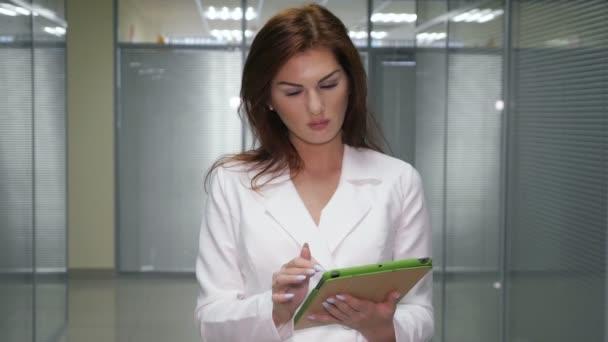 Redhead podnikatelka v obleku s tablet stál na chodbě úřadu