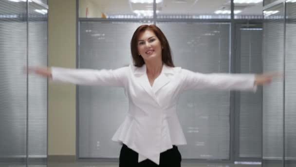 Úspěšná podnikatelka s rukama nahoře na chodbě úřadu