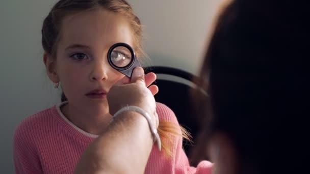 optometrie koncept - lékař s lupou zkoumání holčička