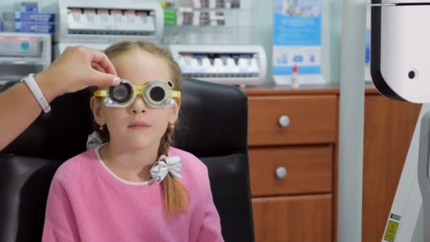 7ed2f352d4dd Young girl is having eye exam performed by optician