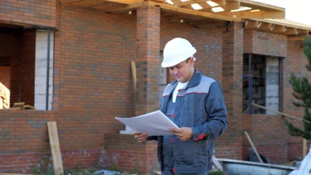 Bauunternehmer mit Plänen draußen vor Ort
