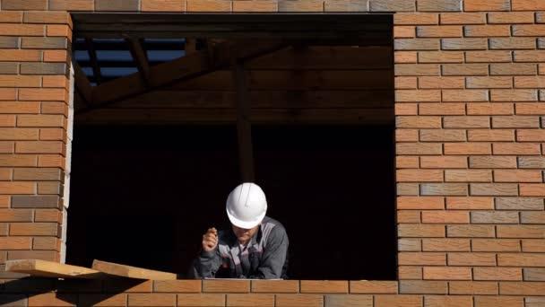 Z pohledu stavebnin v rámu prázdná okna domu pod stavby stojící v slunci a dělal poznámky na papíře