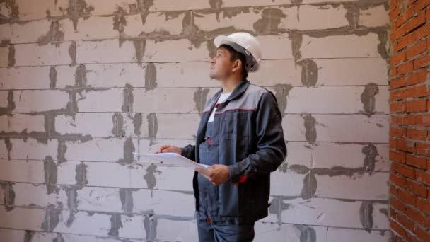 Mann mit Papieren erkundet Raum in im Bau befindlichem Gebäude