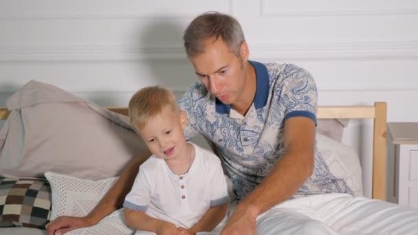 Muž se synem podívat laptop na posteli