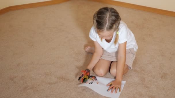 Little girl sitting on floor with papers and drawing with watercolors at home