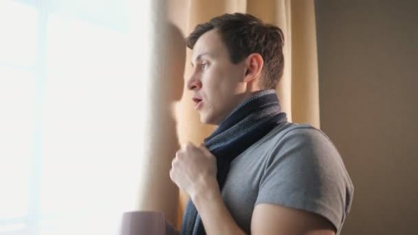 Seitenansicht eines kranken Mannes mit einem Becher Heißgetränk, der am Fenster hustet, Zeitlupe