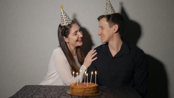 Mladá žena a muž slaví svátek s dortem a svíčky
