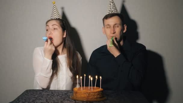 Smiling couple celebrates a holiday playing with party blowers