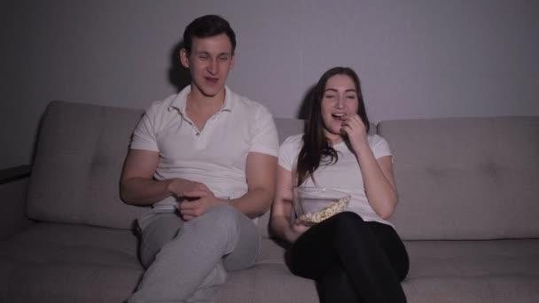 Šťastný pár sledování filmu v televizi, sedí na gauči doma