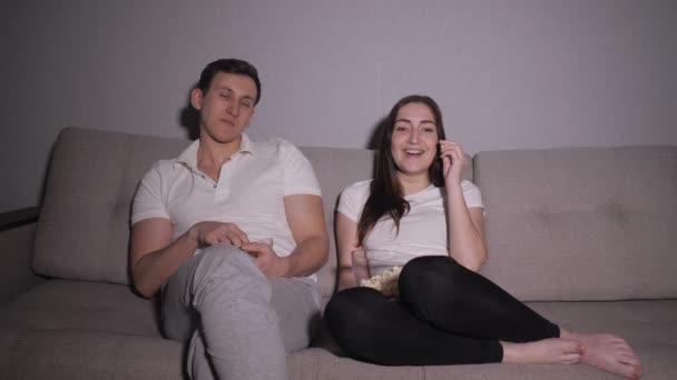 Unavený a znuděný pár líně sedí na pohovce v noci dívat na televizi
