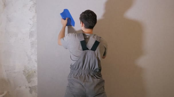 Man applying wallpaper on wall — Stock