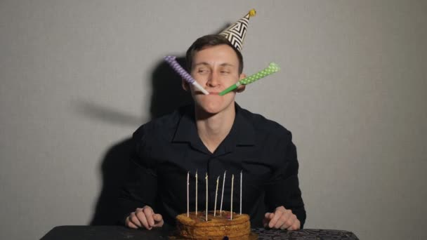 Detailní záběr mladého muže s dortem a svíčkami, hrát si s party dmychadla