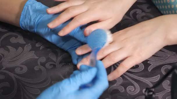 Maniküre reinigt die Fingernägel von Frauenhänden mit einem Pinsel