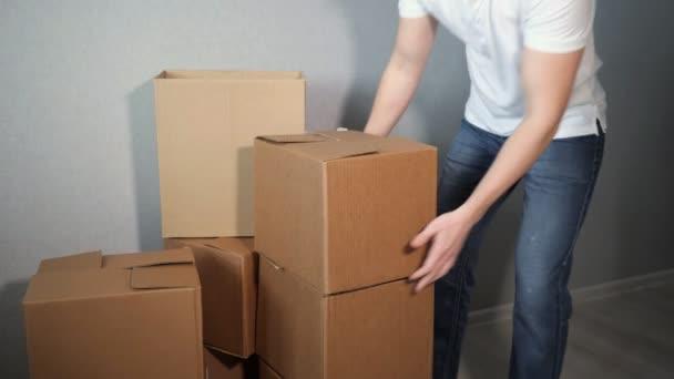 Zeitlupe des Menschen nimmt eine Menge Kartons und Kisten fallen, 4k