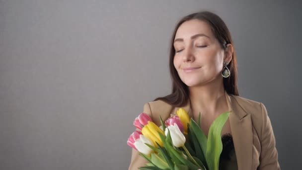 Beautiful girl with a bouquet of tulips, enjoy and looking out the window