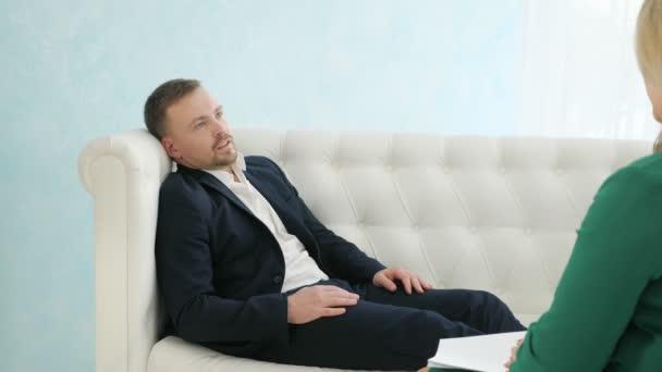 Upset man having consultation with female psychologist