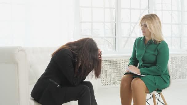 Upset woman having consultation with female psychologist