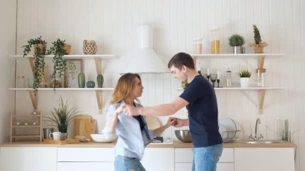 Blonde Mädchen tanzen am Herd in der modernen Küche
