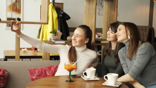 Three girlfriends are making selfie on mobile phone sitting in cafe.
